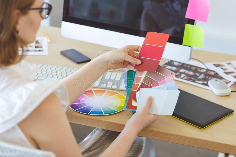 图表设计师检查颜色与颜色样片在书桌 图库摄影