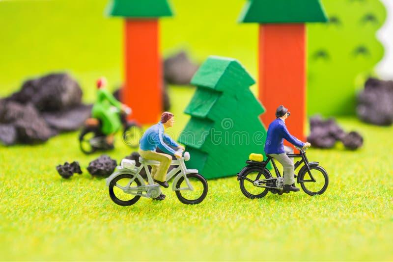 图象人(微型图)有减速火箭的自行车的在公园 免版税库存照片