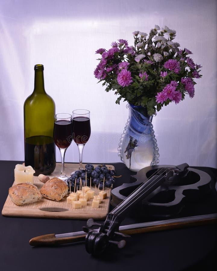 图象瓶酒蜡烛面包葡萄和乳酪小提琴开花 免版税库存照片