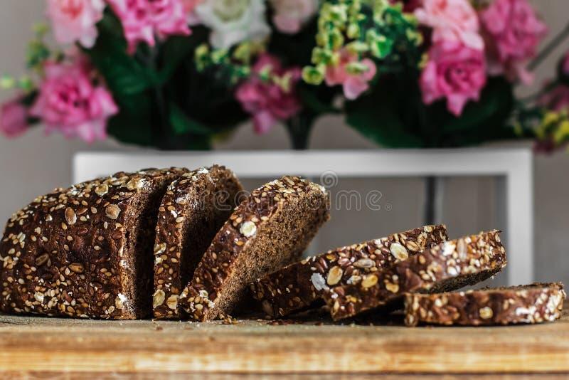 -图象的多五谷板关闭 黑面包切了在花装饰的背景的 免版税库存照片