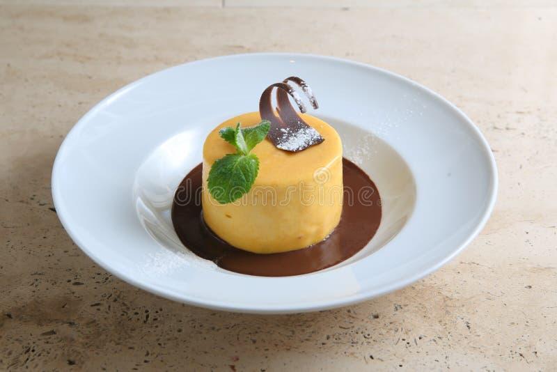 圆形蛋糕用在白色板材的温和巧克力 免版税图库摄影