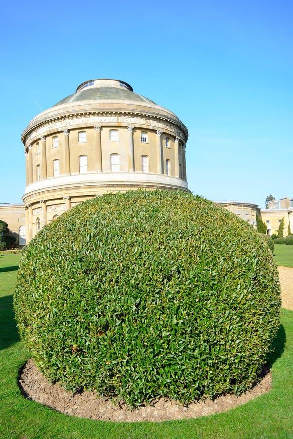 圆形建筑与被整理的树篱 免版税库存图片