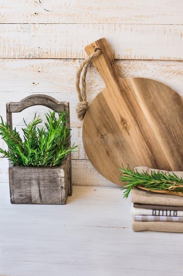 圆材切板,堆亚麻制洗碗布,在葡萄酒箱子的新鲜的迷迭香在白色板条木头背景 免版税库存照片