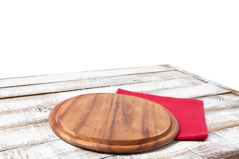 圆材比萨切板和红色餐巾在白色背景隔绝的木桌上 顶视图和拷贝空间,空和 免版税库存图片