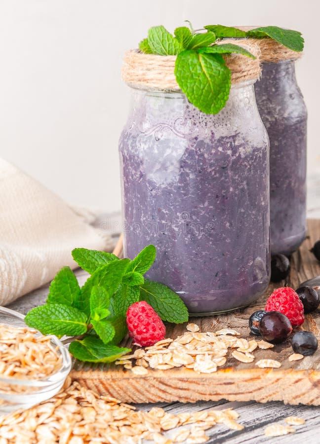 圆滑的人用蓝莓、莓、黑醋栗和薄菏 在原始的玻璃瓶子 压印的木桌 白色洗涤了 免版税库存照片