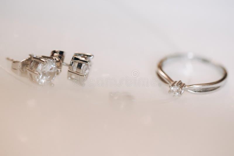 圆环和耳环有金刚石的在白色背景 免版税图库摄影
