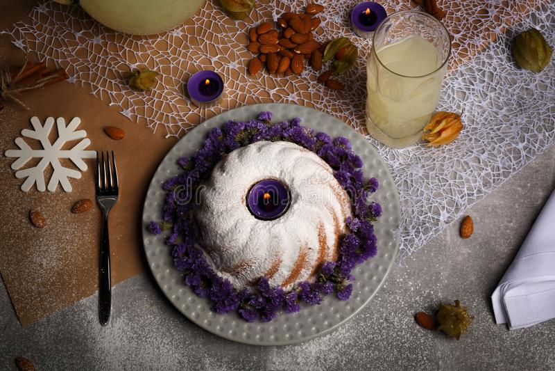 圆环蛋糕洒与糖粉末,杏仁,桂香,在轻的五颜六色的背景的空泡 免版税库存照片