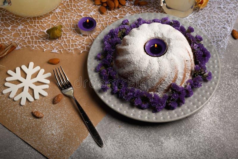 圆环蛋糕洒与糖粉末,杏仁,桂香,在轻的五颜六色的背景的空泡 图库摄影