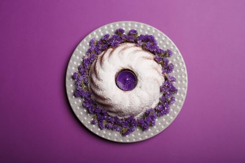 圆环蛋糕的顶视图洒与搽粉的糖,与一个紫罗兰色蜡烛在一个中心在明亮的紫罗兰色背景 免版税库存图片