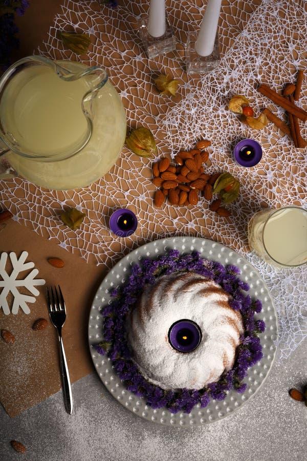 圆环蛋糕的顶视图洒与糖粉末,杏仁,蜡烛,桂香,在轻的五颜六色的背景的空泡 图库摄影