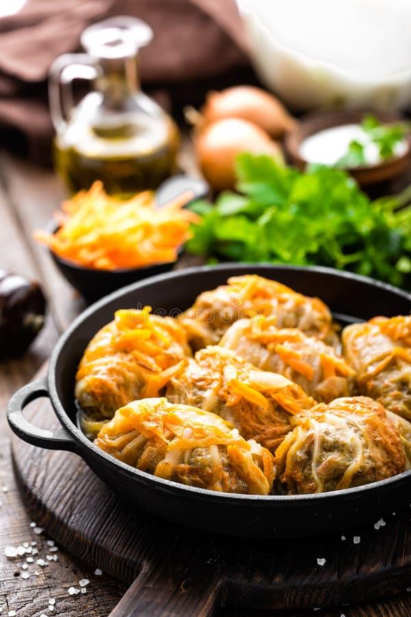 圆白菜卷炖了用肉和菜在平底锅在黑暗的木背景 库存图片