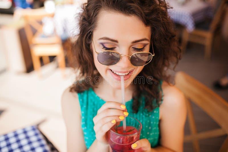 圆的太阳镜的妇女有在获得咖啡馆的大阳台的鸡尾酒的乐趣 免版税库存照片