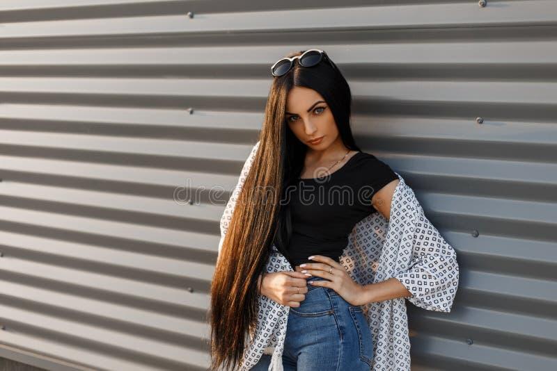 圆的太阳镜的年轻迷人的端庄的妇女有在一件黑时兴的T恤杉的长发的在葡萄酒夏天夹克 图库摄影