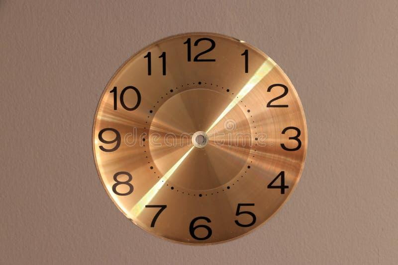 圆的手表面对在灰色背景的钟针 免版税库存照片
