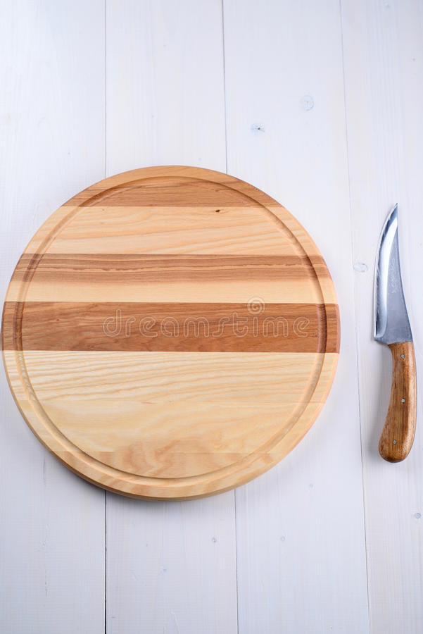 圆的木板和刀子在背景 免版税库存图片