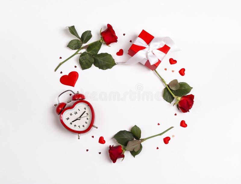 圆的框架由玫瑰色花、礼物、闹钟和装饰心脏做成在白色背景 背景日重点空白st的华伦泰 图库摄影