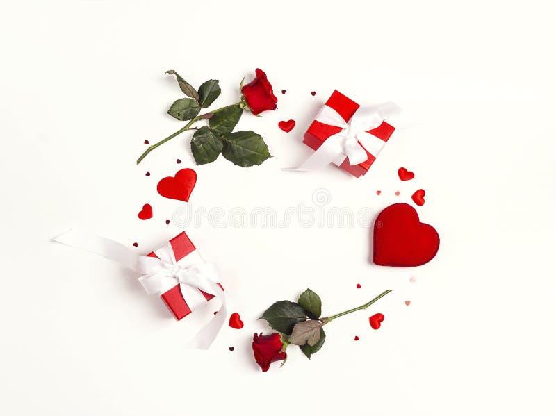 圆的框架由玫瑰色花、礼物和装饰心脏做成在白色背景 背景日重点空白st的华伦泰 免版税图库摄影