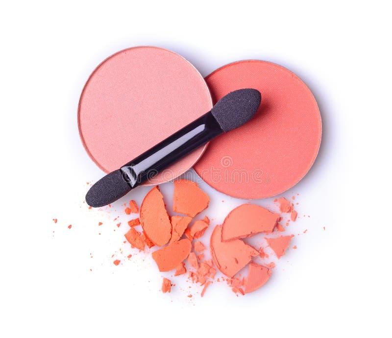 圆的橙色被碰撞的眼影膏和胭脂构成的作为化妆用品产品样品与涂药器 免版税库存图片