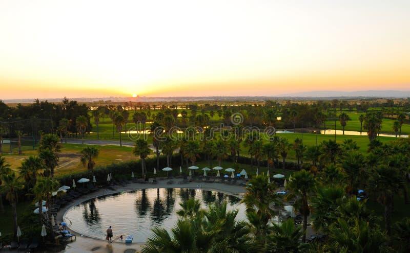 圆的水池和美好的日落风景、高尔夫球场、小湖和树,家庭假日 库存照片