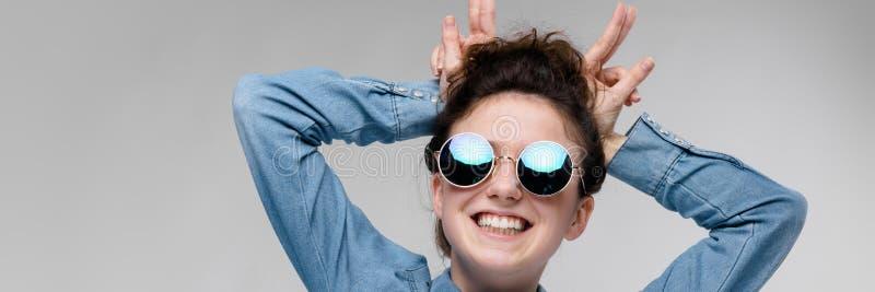 圆的玻璃的年轻深色的女孩 头发在小圆面包被会集 女孩做垫铁 库存图片