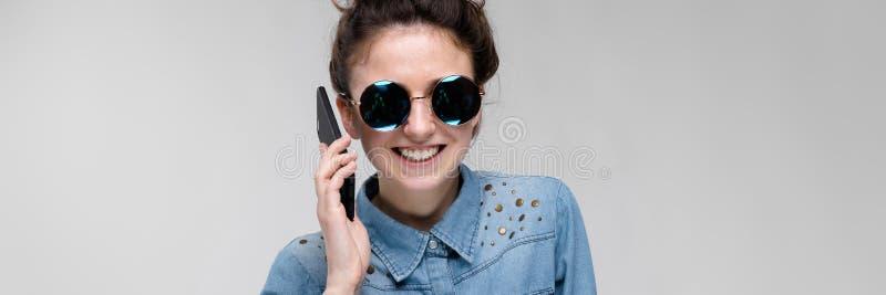 圆的玻璃的年轻深色的女孩 头发在小圆面包被会集 有一个黑电话的女孩 女孩在谈话 免版税库存照片