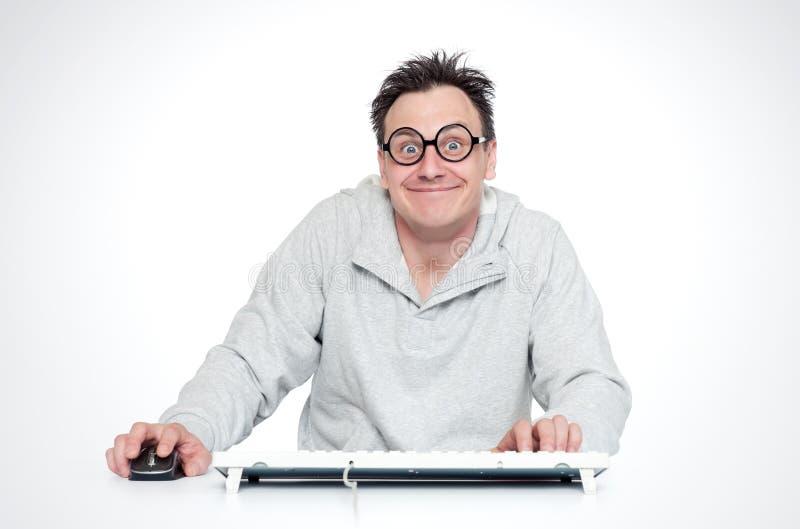 圆的玻璃的愉快的微笑的人坐在与一只键盘和老鼠的一张桌上在计算机前面 满意的程序员 免版税库存图片