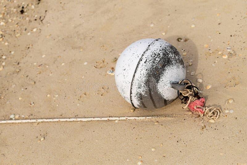 圆的白色多苯乙烯浮体一点被栓对钓鱼在湿沙子背景海洋设计海滩钓鱼的绳索网络鱼 免版税库存图片