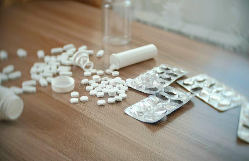 圆的白色片剂和卵形药片在桌上与空的箱子和水泡 图库摄影
