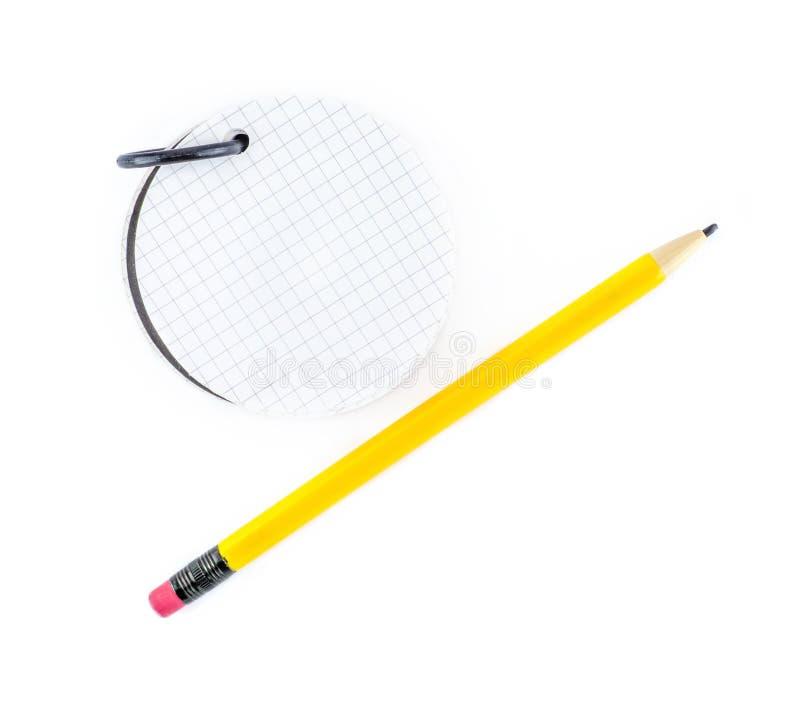 圆的笔记薄和黄色铅笔在白色背景 免版税库存图片