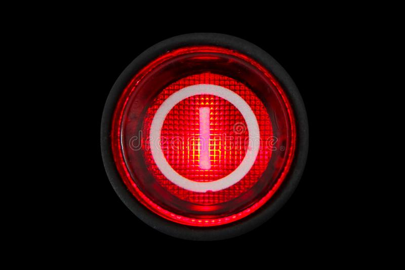 圆的红色力量断断续续的按钮或开关有发光在黑暗的宏观摄影的减速火箭的轻的照明的 免版税库存图片