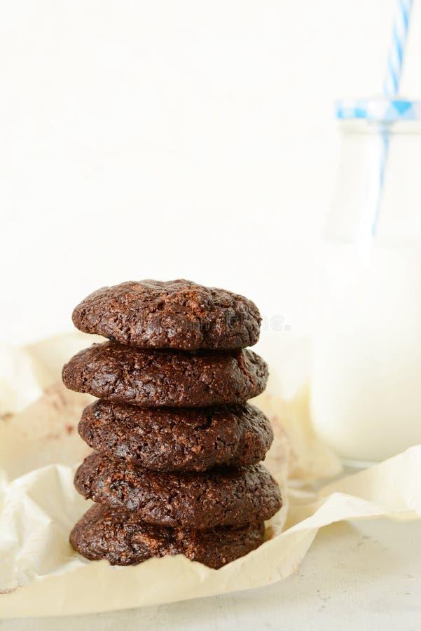圆的被烘烤的巧克力饼干和一个瓶在轻的背景的牛奶 库存照片