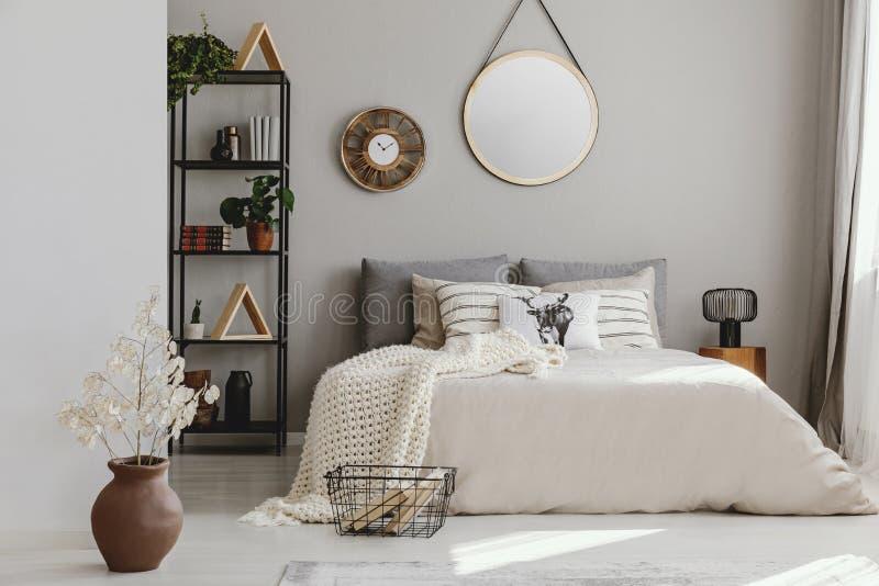 圆的镜子和时钟在床上与枕头在明亮的卧室内部与花 免版税库存照片