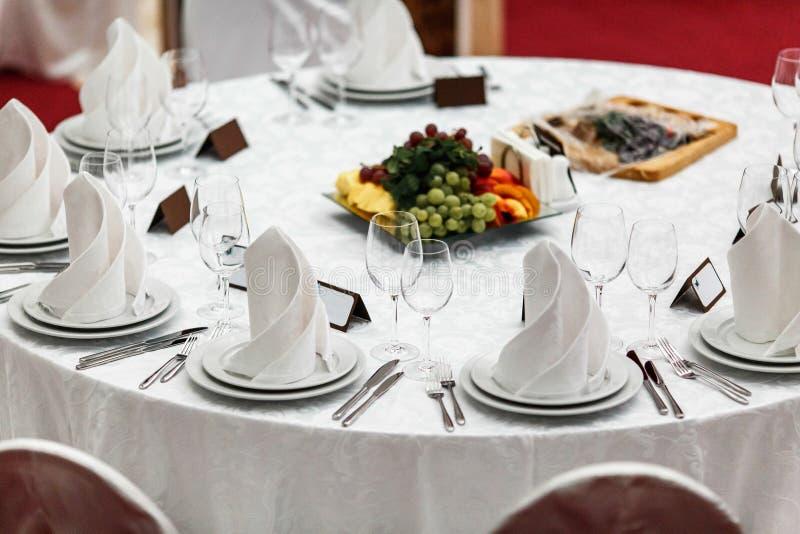 圆的餐馆桌服务了一顿欢乐晚餐的豪华 免版税库存照片