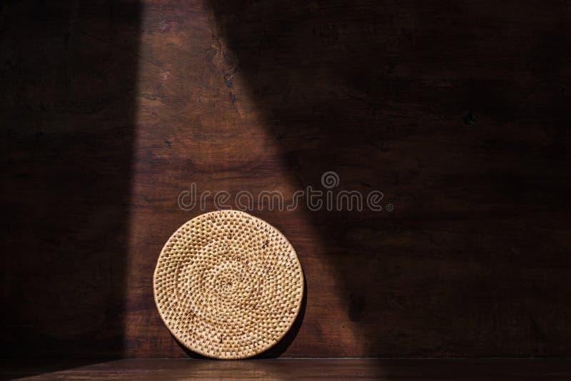 圆的织法藤条盘子,乡下家庭,在减速火箭的木背景与树荫和阴影,阴影环境在 免版税图库摄影