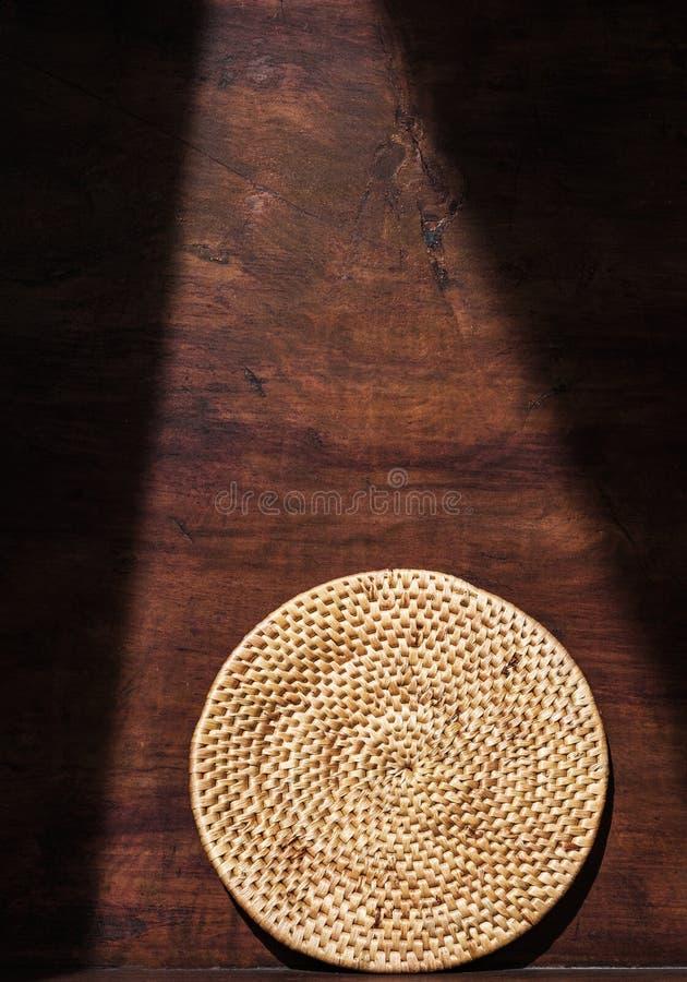 圆的织法藤条盘子,乡下家庭,在减速火箭的木背景与树荫和阴影,阴影环境在 免版税库存照片