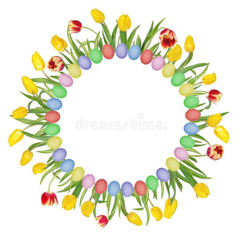 圆花卉框架由美丽的红色和黄色郁金香和五颜六色的复活节彩蛋制成 r 免版税库存图片