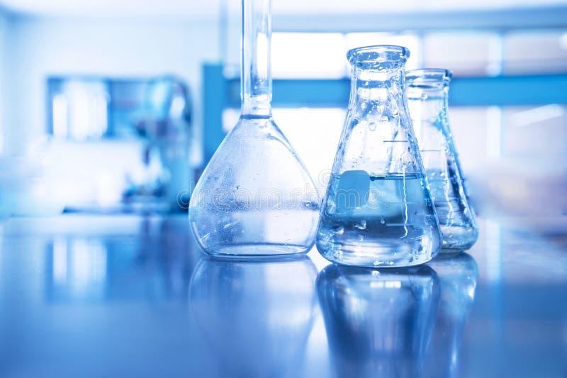 圆锥形和容量玻璃烧瓶在蓝色教育技术背景的科学实验室 免版税图库摄影