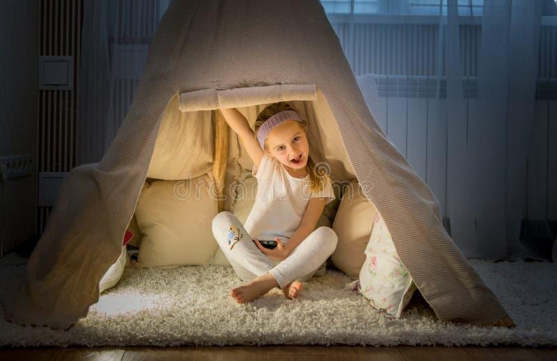 圆锥形帐蓬帐篷的小女孩在屋子里 免版税图库摄影