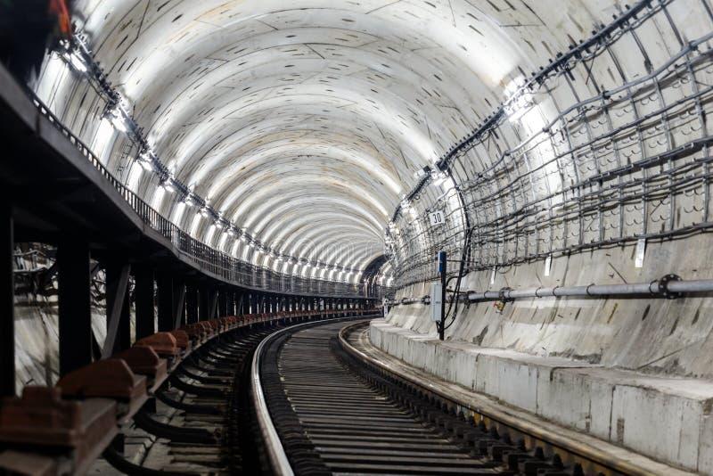 圆隧道地铁路轨和睡眠者向右转和照亮与白光 库存照片