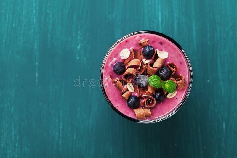 圆滑的人、点心、酸奶或者奶昔健康早餐用冷冻蓝莓和燕麦装饰了被磨碎的巧克力和薄菏 免版税图库摄影