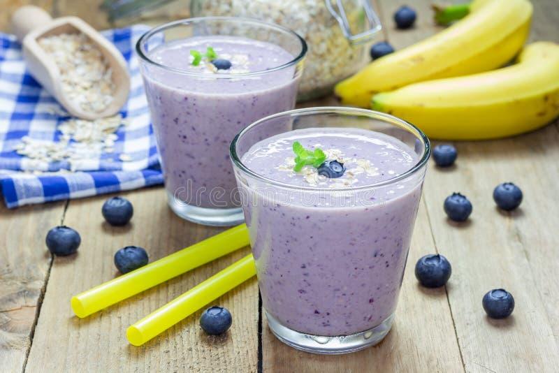 圆滑的人用蓝莓、香蕉、燕麦、杏仁牛奶和酸奶 库存图片
