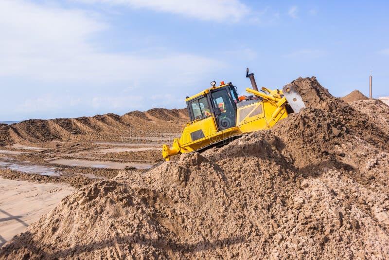 土堤推挤沙子的打瞌睡的人机器 库存照片