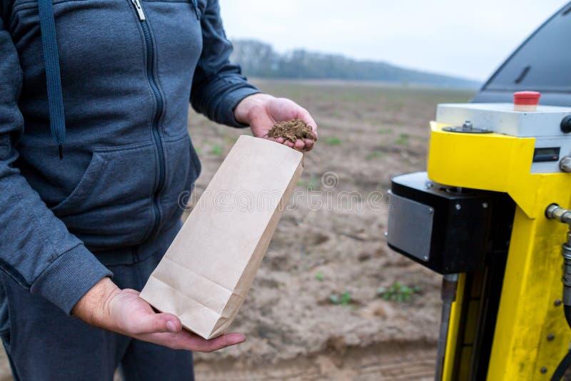 土壤采样 研究实验室的工程师雇员包装在纸包裹的土壤样品 土壤的自动化的探针 免版税库存照片