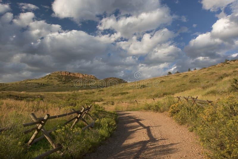 土山麓小丘岩石山的路 免版税库存照片