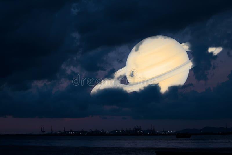 土星支持剪影云彩在海的日落天空,概念萨图 库存照片