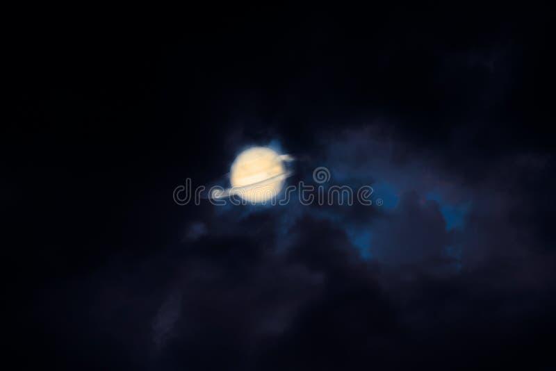土星支持剪影云彩日落天空,在耳朵附近的概念土星 图库摄影