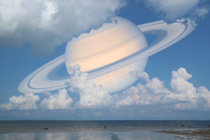 土星支持在海,在地球附近的概念土星的云彩天空 库存照片