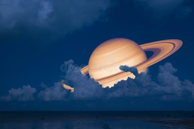 土星支持夜云彩在海,在E附近的概念土星的日落天空 库存图片