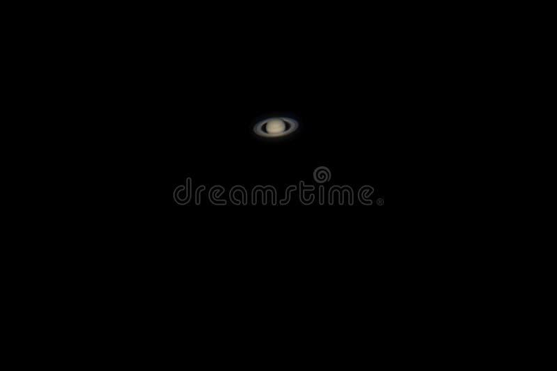 土星行星真正的照片与望远镜的 免版税库存照片