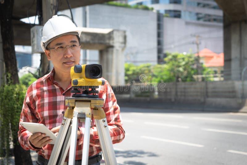 土木工程师与tacheometer或经纬仪equipm的土地调查 库存图片